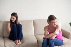 Two young angry women sitting apart on sofa royalty free stock photo