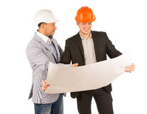 Two young architects discussing a building plan. Two young architects or structural engineers standing discussing a building plan or blueprint smiling happily as royalty free stock image