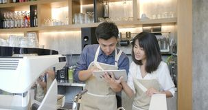 Two young asian barista man and woman using tablet computer during a break on the work in the coffee shop