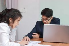 Two young Asian business people analyzing paper work or charts together in modern office. Team work business concept. Selective fo. Cus and shallow depth of Royalty Free Stock Image