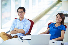 Two young asian businesspeople in office. Two young asian businesspeople looking at camera smile in the office Stock Photo