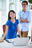Two young asian businesspeople in office. Two young asian businesspeople looking at camera smile in the office Royalty Free Stock Images