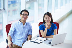 Two young asian businesspeople in office. Two young asian businesspeople looking at camera smile in the office Stock Photos