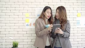 Two young Asian businesswoman college students or coworkers drinking coffee and talking in office, diverse group. stock video footage