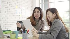Two young Asian businesswomen working together in office at small business sitting reading a report or paperwork with pleased. stock video