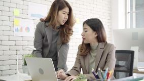 Two young Asian businesswomen working together in office at small business sitting reading a report or paperwork with pleased. stock video footage