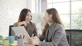 Two young Asian businesswomen working together in office at small business sitting reading a report or paperwork.