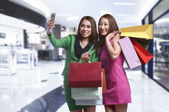 Two young asian female with shopping bag taking selfie Royalty Free Stock Images