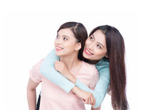 Two young asian girlfriends in hoodies having fun together. Whit Stock Photography