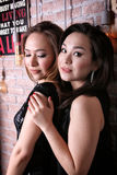 Two young asian girls models hugging royalty free stock image