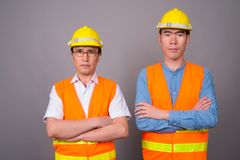 Two young Asian men construction worker together against gray ba stock photos