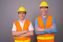Two young Asian men construction worker together against gray ba royalty free stock images