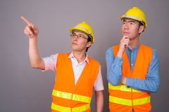 Two young Asian men construction worker together against gray ba stock photo