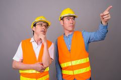 Two young Asian men construction worker together against gray ba royalty free stock photos