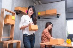 Two young Asian people startup small business entrepreneur SME d. Istribution warehouse with parcel mail box. small  owner home office. Online marketing and Royalty Free Stock Photography