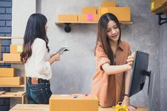 Two young Asian people startup small business entrepreneur SME d. Istribution warehouse with parcel mail box. small  owner home office. Online marketing and Stock Image
