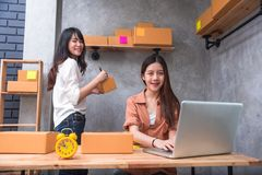 Two young Asian people startup small business entrepreneur SME d. Istribution warehouse with parcel mail box. small  owner home office. Online marketing and Royalty Free Stock Images