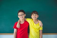 Student standing and smiling in front of chalkboard Stock Photo
