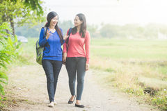 Two young Asian students chatting while walking together Stock Photography