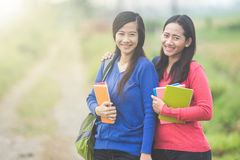 Two young Asian students holding books, smiling brightly to the Stock Images