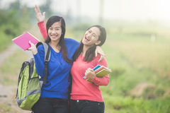 Two young Asian students holding books, smiling brightly to the Royalty Free Stock Photos