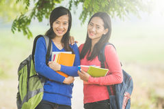 Two young Asian students holding books, smiling brightly to the Stock Image