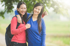 Two young Asian students laugh, joking around together Royalty Free Stock Photo