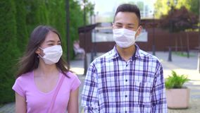 Two young asian students in a medical mask on his face walking down the street and talking close up slow mo stock video