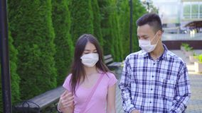 Two young asian students in a medical mask on his face walking down the street and talking close up stock video footage
