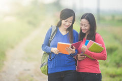 Two young Asian students reading something on the book Stock Images