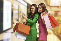 Two young asian woman with shopping bag looking at mobile phone Royalty Free Stock Photos