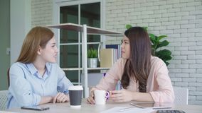 Two young Asian women college students or coworkers drinking coffee and talking in office, diverse group. stock video