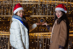 Two Young Asian women posing against the backdrop of a Christmas tree with garlands to night. Stock Image