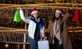 Two Young Asian women posing against the backdrop of a Christmas tree with garlands to night. After shopping Royalty Free Stock Image