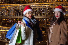 Two Young Asian women posing against the backdrop of a Christmas tree with garlands to night. Royalty Free Stock Photos