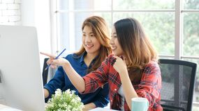 Two young asian women working with computer at home office with happy emotion, working at home, small business, office casual. Lifestyle, adult learning online royalty free stock image