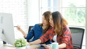 Two young asian women working with computer at home office with happy emotion, working at home, small business, office casual. Lifestyle, adult learning online royalty free stock photos