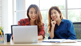 Two young asian women working with laptop computer at home office with happy emotion moment, working at home, small business,. Office casual lifestyle concept royalty free stock image