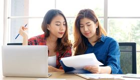 Two young asian women working with laptop computer at home office with happy emotion moment, working at home, small business,. Office casual lifestyle concept stock photos