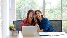 Two young asian women working with laptop computer at home office with happy emotion moment, working at home, small business,. Office casual lifestyle concept stock image