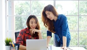 Two young asian women working with laptop computer at home office with happy emotion moment, working at home, small business,. Office casual lifestyle concept royalty free stock photography