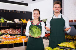 Two young assistants displaying vegetables. Of grocery shop royalty free stock photos