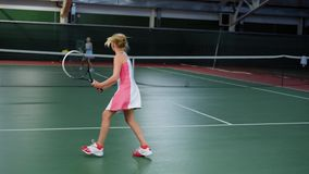 Two young athletes jumping in recreation area playing sport game. Three happy children having tennis lesson improving. Back view of two young athletes jumping in stock footage