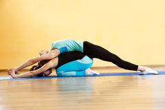 Two young athletes practicing yoga. In gym Stock Photography