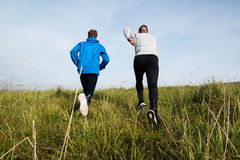 Two young athletes running in sunny autumn nature, rear view. Stock Images