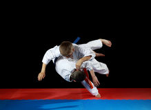 Two young athletes in the sharp drop perform judo throw. Young athletes in the sharp drop perform judo throw royalty free stock photography