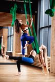 Two young athletic girls brunette and blonde are doing fitness on the green aerial silk in the modern gym stock images