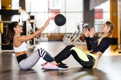 Two young athletic girls dressed in sportswear are doing together sport exercises for press with fitness ball in the stock image