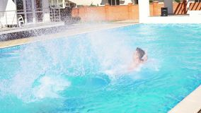 Two young athletic men in swimshorts running and jumping to the swimming pool turning around. Slow motion shot. stock video