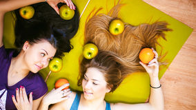 Two young athletic physique women in gym Lie on the floor on yoga mats Stock Images